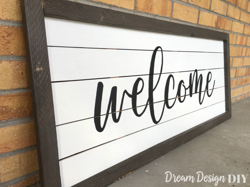 See how easy it is to get the look of shiplap with this DIY large framed shiplap welcome sign. Put your favorite words or quotes or display a wreath. Hang several in different sizes throughout your home. Get this easy tutorial to learn how to make your own. #shiplapsign #woodsign #farmhouse #diy