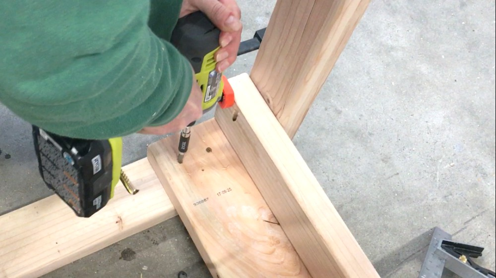 Attaching legs to frame of DIY garage workbench.