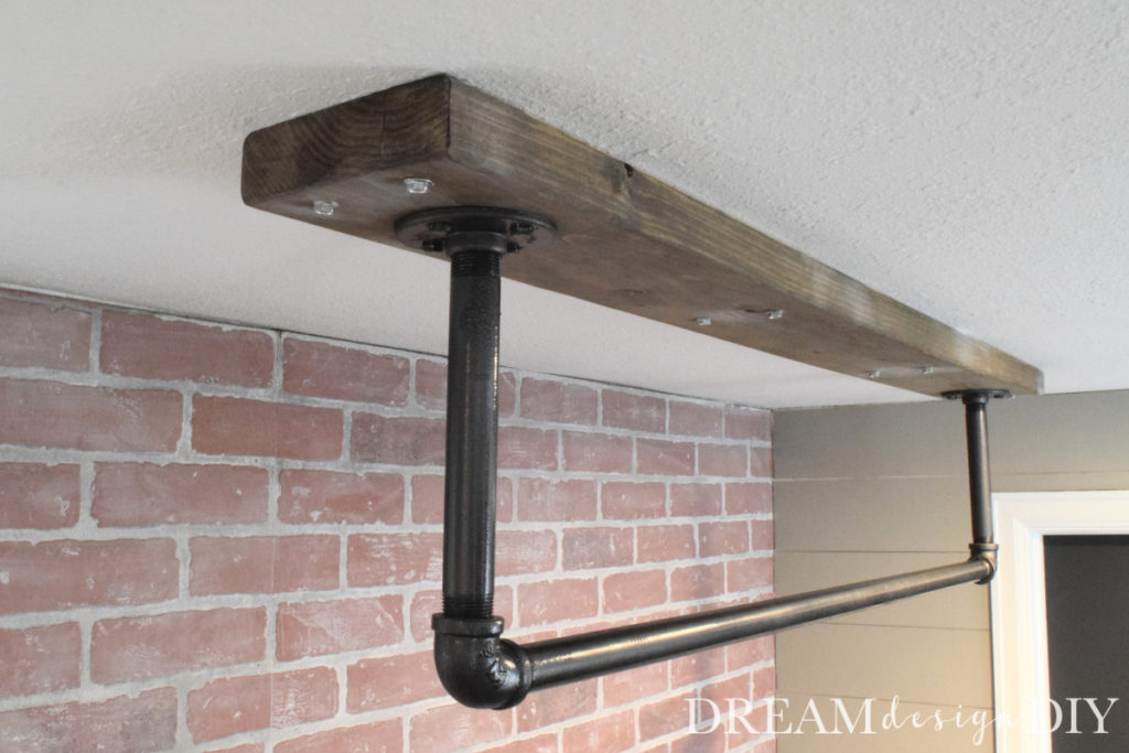 A ceiling mounted pull up bar is a perfect addition to a home gym. Here is a detailed tutorial to make your own. #pullupbar #ceilingmountedpullupbar #diypullupbar