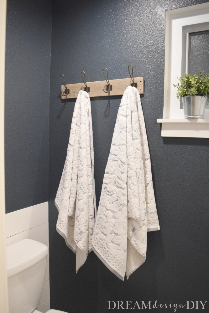 Make this easy pallet towel rack from a pallet or piece of scrap wood. These towel hooks are perfect for quickly hanging bath towels while also looking stylish. Add some pretty patterned towels to add character to your bathroom walls. The stained wood and vintage hooks add a rustic, farmhouse or industrial look. #pallet #DIY #bathroom #hooks
