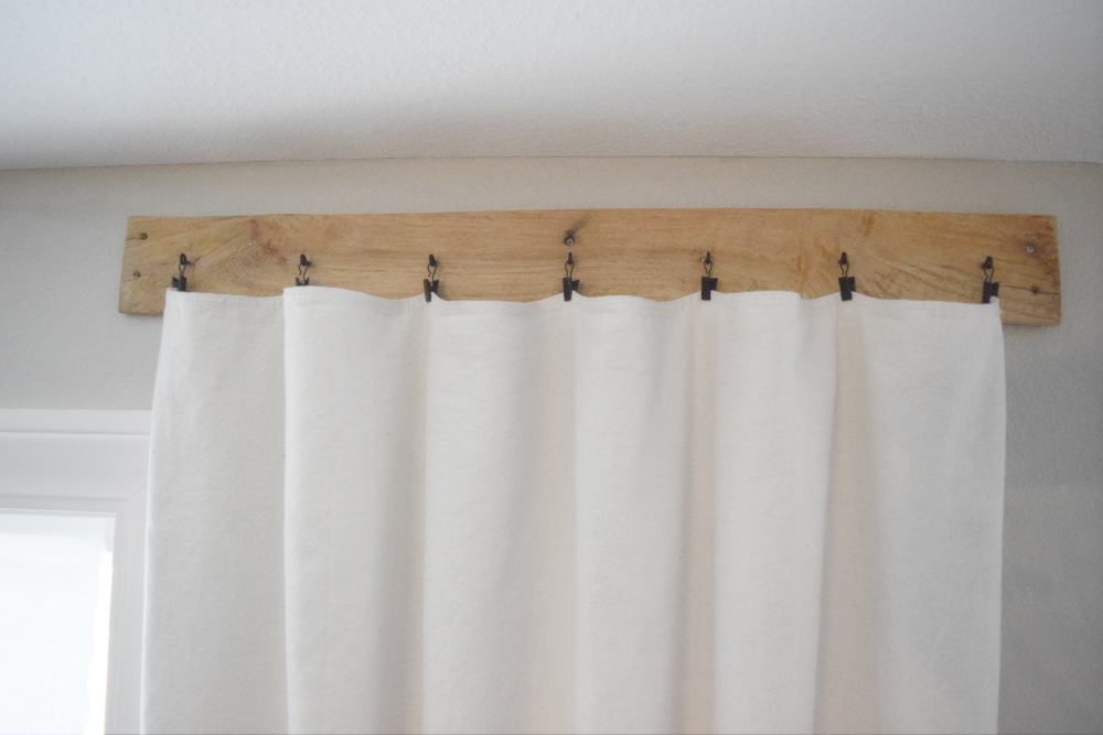 Here is a simple solution for styling your windows. Make these easy and inexpensive pallet curtain rods that add a rustic farmhouse style to your windows. These are a great solution for those large windows that require long curtain rods. #pallets #curtains #curtainrods #diy #farmhouse
