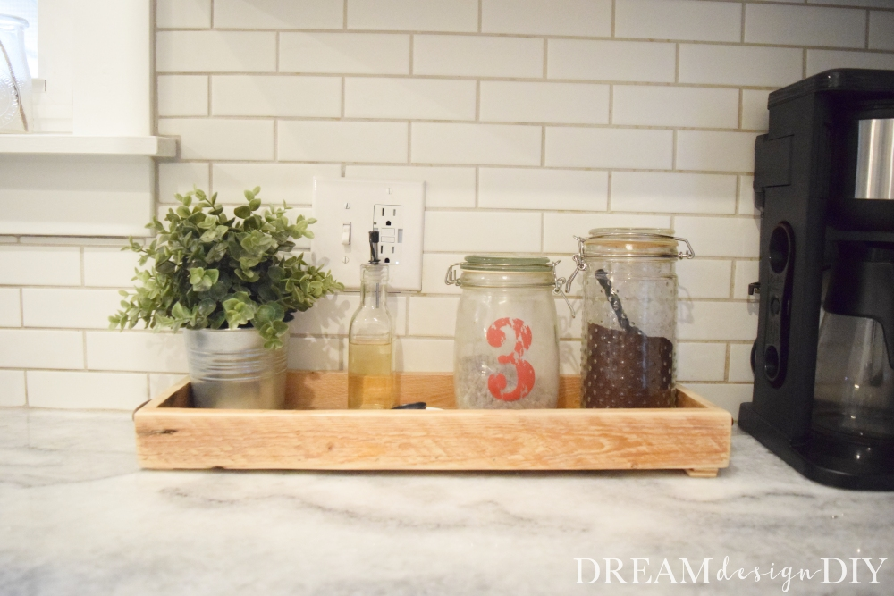 Keep all of your coffee essentials together with this easy DIY wood tray made from pallets. This simple rustic tray adds character to your kitchen while also keeping your counter area organized. Attach decorative handles for additional charm. This tray is versatile. Add some greenery and some small accessories and now you have a centerpiece for a table. #tray #woodtray #coffeetray #diy