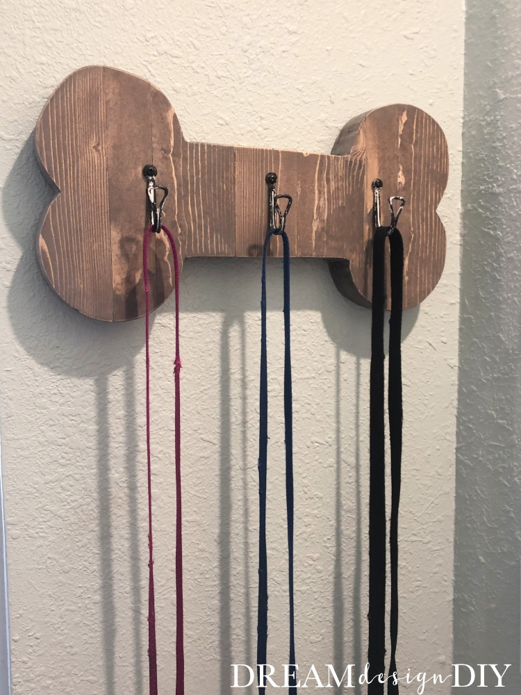 This DIY dog leash holder is wall mounted with hooks making it easy to store your's dog leashes and head out the door for their daily walk. The bone cutout, included in the post, ads character to the holder. #diy #dogleashholder #woodworking